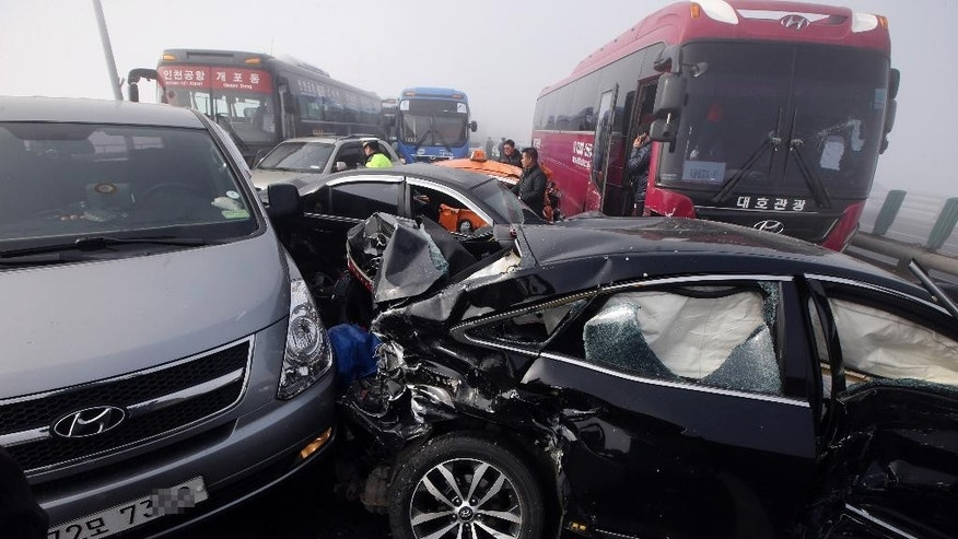 Damaged vehicles sit on Yeongjong Bridge in Incheon, South Korea, Wednesday, Feb. 11, 2015. Two people were killed and at least 42 were injured on Wednesday after a pileup involving about 100 vehicles in foggy weather on the bridge near the Incheon International Airport, South Korean officials said. (AP Photo/Yonhap, Suh Myung-gon) KOREA OUT