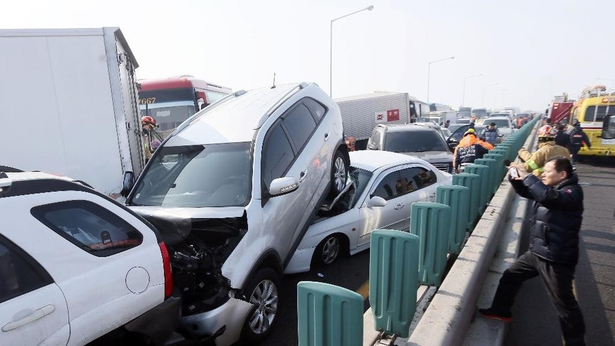 Damaged vehicles sit on Yeongjong Bridge in Incheon, South Korea, Wednesday, Feb. 11, 2015. Two people were killed and at least 42 were injured on Wednesday after a pileup involving about 100 vehicles in foggy weather on the bridge near the Incheon International Airport, South Korean officials said. (AP Photo/Yonhap, Yun Tae-hyun) KOREA OUT