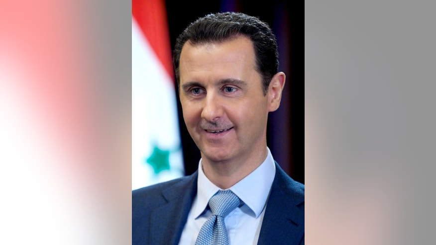 In this photo released on Tuesday, Feb. 10, 2015, by the Syrian official news agency SANA, Syrian President Bashar Assad smiles during an interview with the BBC, in Damascus, Syria. Assad said in comments published Tuesday that his government has been receiving general messages from the American military about airstrikes targeting the Islamic State group inside Syria but that there is no direct cooperation. (AP Photo/SANA)