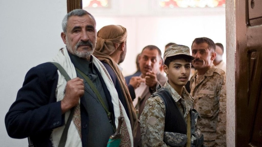 Houthi Shiite Yemenis stand guard at the parliament during a meeting in Sanaa, Yemen, Monday, Feb. 9, 2015. Yemens Shiite rebels are meeting with political rivals for the first time since cementing their power grab last week by dissolving parliament and making their top security body the de facto government. (AP Photo/Hani Mohammed)