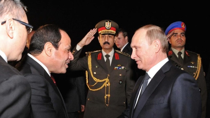 In this image released by the Egyptian Presidency, Egyptian President Abdel-Fattah el-Sissi, left, shakes hands with Russian President Vladimir Putin upon his arrival at the Cairo International Airport in Egypt, Monday, Feb. 9, 2015. Putin arrived in Cairo on Monday to meet his Egyptian counterpart, with both sides eager to strengthen ties and show both have options outside of the West to pursue their goals. The visit, the first by Putin to Egypt in a decade, is largely symbolic, analysts say. (AP Photo/Ahmed Fouad, Egyptian Presidency)