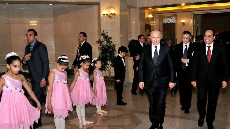 In this image released by the Egyptian Presidency, Egyptian President Abdel-Fattah el-Sissi, right, walks with Russian President Vladimir Putin at the Cairo Opera House in Egypt, Monday, Feb. 9, 2015. Putin arrived in Cairo on Monday to meet his Egyptian counterpart, with both sides eager to strengthen ties and show both have options outside of the West to pursue their goals. The visit, the first by Putin to Egypt in a decade, is largely symbolic, analysts say. (AP Photo/Egyptian Presidency)