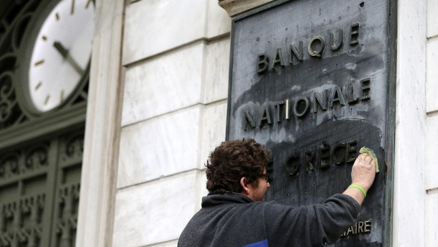"A worker cleans a marble sign that reads in French ''National Bank of Greece'' in Athens, on Monday, Feb. 9, 2015. Investors hammered Greece's markets Monday after the country's new government renewed a pledge to seek bailout debt forgiveness and dubbed the rescue package a ""toxic fantasy"" — comments that presage a clash with European lenders at high-stakes meetings this week. (AP Photo/Thanassis Stavrakis)"