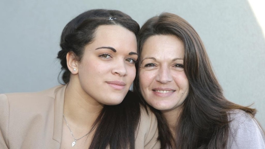 Sophie Serrano, right, poses with her daughter Manon,Tuesday, Feb.10, 2015, in Grasse, southeastern France. A nurse's assistant had accidentally given baby Manon Serrano, who was in an incubator, to another mother after her birth in July 1994, and given the infant next to her to Sophie Serrano. A court on Tuesday ordered a private clinic in the Riviera city of Cannes to pay out 400,000 euros ($450,000) each to two 20-year-old girls accidentally switched at birth and given to the wrong parents — part of a 1.88-million euro payment to members of the two families. (AP Photo/Lionel Cironneau)