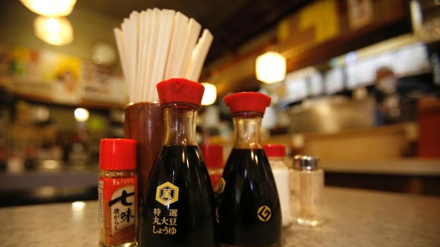 Soy sauce bottles are placed on the table with chopsticks and other condiments at a restaurant in Tokyo Tuesday, Feb. 10, 2015. It's a simple glass bottle with a red top that has become a symbol of soy sauce in Japan and much of the world. More than half a century after its creation, the Kikkoman soy sauce bottle remains a familiar and comforting shape on restaurant and dining room tables in many countries. The bottle's designer, Kenji Ekuan, died Saturday, Feb. 7 of a heart condition at age 85. Japanese on the bottle reads: Premium unprocessed soybeans soy sauce. Japanese on the red bottle reads: Seven flavored red pepper. (AP Photo/Shizuo Kambayashi)