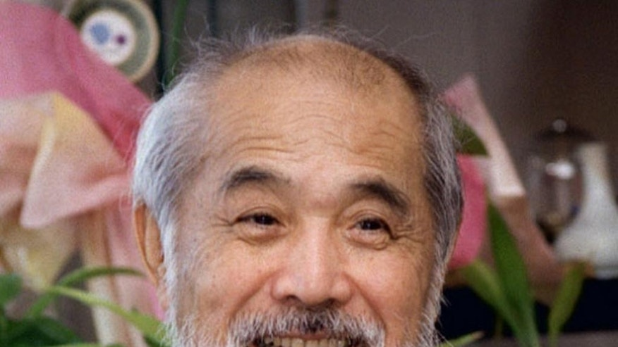 This 2003 photo shows Japanese industrial designer Kenji Ekuan in Tokyo. Ekuan, whose works ranged from a bullet train to the red-capped Kikkoman soy sauce dispenser as familiar as the classic Coca-Cola bottle, has died, his company said on Monday, Feb. 9, 2015. He was 85. Ekuan, a former monk, crafted a tabletop bottle for Kikkoman Corp. in 1961, winning international popularity both for the handy, flask-shaped dispenser and of course for the salty brown condiment flavoring many Asian cuisines. (AP Photo/Kyodo News) JAPAN OUT, CREDIT MANDATORY