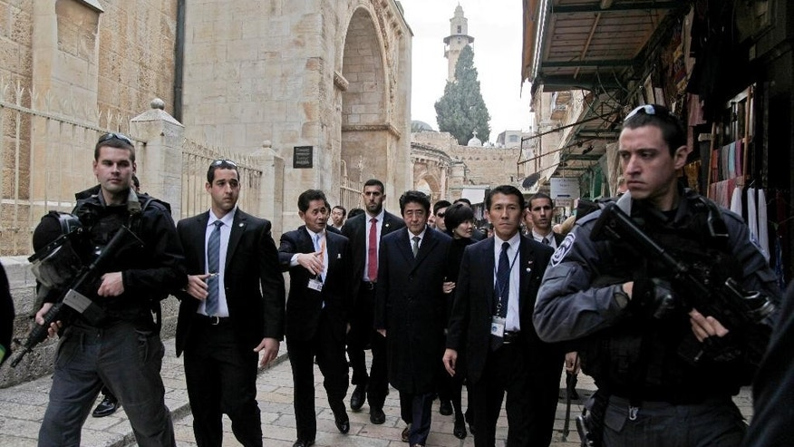 FILE - In this Jan. 19, 2015 file photo, Japanese Prime Minister Shinzo Abe, center, and his wife Akie walk together, escorted by armed security guards during a visit to Jerusalem's Old City as part of his six-day visit to the Middle East. Japan's outrage over the slaying of two Japanese hostages by the Islamic State group is settling into a heightened awareness of risks associated with the country's pursuit of lucrative energy projects and other economic ties in the Middle East. (AP Photo/Mahmoud Illean, File)