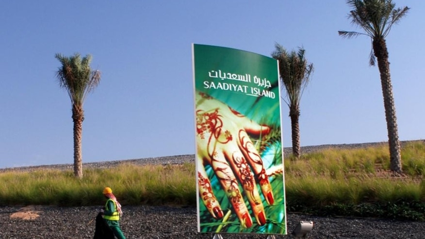 This 2009 image released by the Human Rights Watch, shows a laborer next a to Saadiyat Island advertising billboard in Abu Dhabi, United Arab Emirates. Reforms enacted in the United Arab Emirates have not done enough to end the exploitation of migrant workers building a high-profile cultural complex that includes branches of the Louvre and the Guggenheim museums, a leading human rights group said Tuesday in a report that was immediately rejected by the government-backed developer. (AP Photo/Samer Muscati, Human Rights Watch)