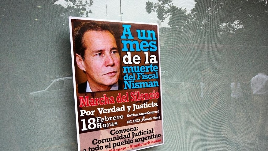 A poster announcing a march organized by federal prosecutors in demand for justice to commemorate the first month after the death of prosecutor Alberto Nisman, is seen on a window in Buenos Aires, Argentina,Tuesday, Feb. 10, 2015. Nisman's mysterious death came as he was presenting allegations that Argentine President Cristina Fernandez had conspired to protect Iranian officials implicated in the 1994 bombing of a Jewish community center in which 85 people died. Fernandez and Iran have denied the allegations.  (AP Photo/Rodrigo Abd)