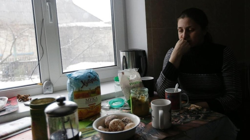 In this picture taken, Monday, Feb. 9, 2015, Sveta Banina sits in her kitchen in Donetsk. Day and night, mortars and rockets rain down on the rebel stronghold in eastern Ukraine _ mainly in the city's outlying districts, where the poorest people live. (AP Photo/Petr David Josek)