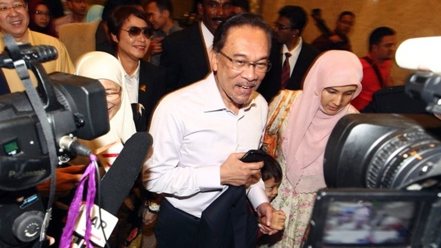 Feb. 10, 2015: Malaysian opposition leader Anwar Ibrahim, center, arrives at court house in Putrajaya. Malaysia's top court on Tuesday upheld Anwar's sodomy conviction in a case seen at home and aboard as politically motivated to eliminate any threats to the government. (AP Photo)