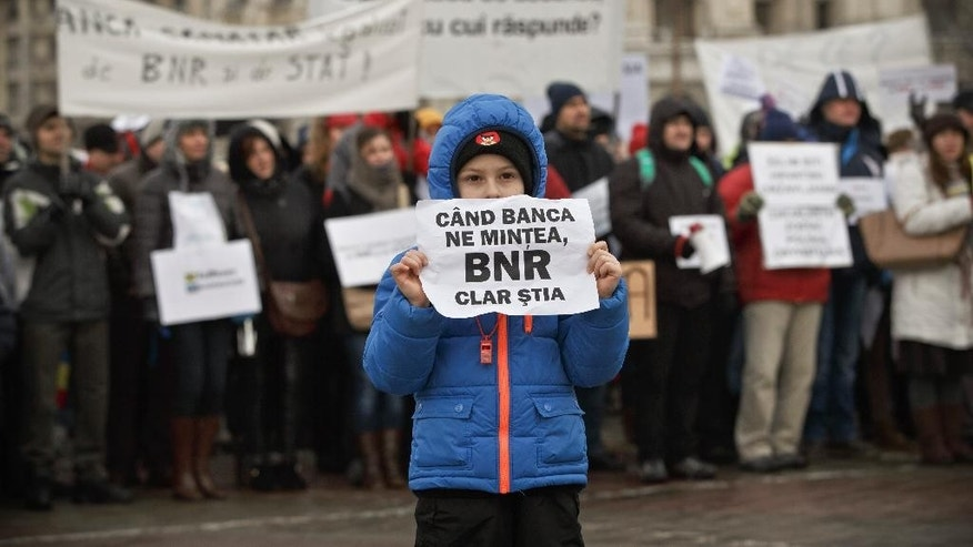 "FILE - In this Feb. 8, 2015 file picture a child from a Romanian family that has  contracted a Swiss francs loan holds a paper that translates ""The National Bank knew the banks were lying to us""  during a protest outside the parliament building in Bucharest, Romania. On Jan. 15, the Swiss national bank unpegged the franc from the euro, causing the currency to surge. That move by one of Europe's richest countries is adding to the financial despair of hundreds of thousands of people across some of the poorest regions of the continent due to mortgages taken out years ago in Swiss francs.(AP Photo/Vadim Ghirda, File)"