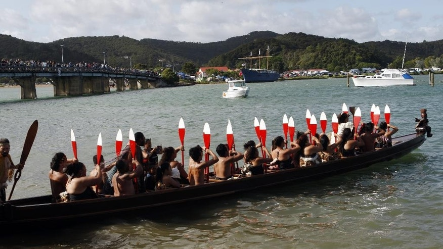 In this Feb. 5, 2014 photo, a crowd watches from a bridge as canoeists hold their paddles aloft in a traditional Maori canoe, or waka, in Waitangi, New Zealand. The nation celebrated the 175th anniversary of the signing of the Treaty of Waitangi, the country's founding document, over a three-day weekend. (AP Photo/Nick Perry)