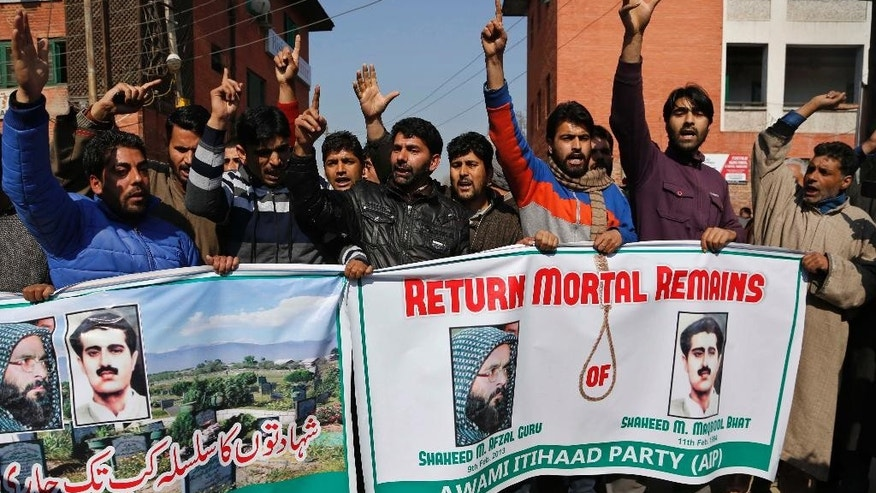 Kashmiri activists of Awami Itihaad party shout slogans as they hold banners with photographs of pro-independence leader Mohammed Maqbool Butt, right and former Kashmiri rebel Mohammed Afzal Guru during a protest in Srinagar, India, Monday, Feb. 9, 2015. Anti India separatists called for a strike Monday to mark the anniversary of the execution of Guru who was hanged in secret in a New Delhi jail two years ago.Separatists have called for another strike on Wednesday to mark the 1984 hanging of pro-independence leader Mohammed Maqbool Butt, who was executed for killing an intelligence officer. (AP Photo/Mukhtar Khan)