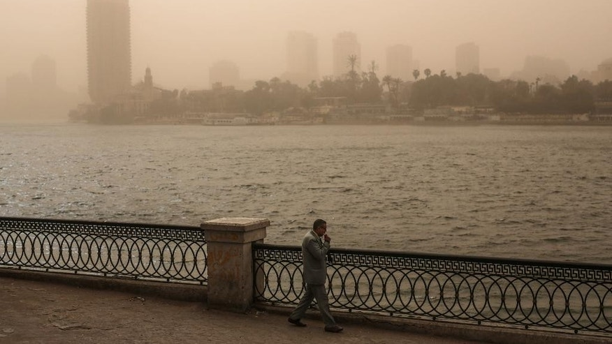 A man walks on the Nile corniche during a sandstorm in Cairo, Egypt, Tuesday, Feb. 10, 2015. Egyptian officials say Cairo International Airport has been closed to arrivals amid a developing sandstorm. The sandstorm hit Egypt Tuesday after unusually warm and sunny weather for February. The sky over downtown Cairo turned yellow and blotted out the sun, limiting visibility. (AP Photo/Mosa'ab Elshamy)