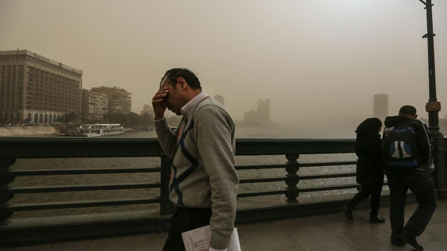 People walk on a bridge during a sandstorm in Cairo, Egypt, Tuesday, Feb. 10, 2015. Egyptian officials say Cairo International Airport has been closed to arrivals amid a developing sandstorm. The sandstorm hit Egypt Tuesday after unusually warm and sunny weather for February. The sky over downtown Cairo turned yellow and blotted out the sun, limiting visibility. (AP Photo/Mosa'ab Elshamy)