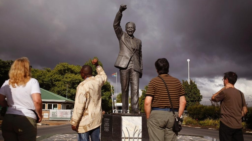 A tour guide, second left, speaks to French tourists as he, mimics the statue of former South African President Nelson Mandela with a raised fist outside the former Victor Verster prison, renamed to Drakenstein Correctional center near the town of Franschhoek, South Africa, Tuesday, Feb. 10, 2015.  On Feb. 11, 1990,  former South African President Nelson Mandela walked free from the Victor Verster prison with his then wife Winnie Madikizela-Mandela, with a raised fist in the air after being jailed for 27 years by the former South African Apartheid Government. Tomorrow marks the 25th anniversary of Mandela's release from prison. (AP Photo/Schalk van Zuydam)