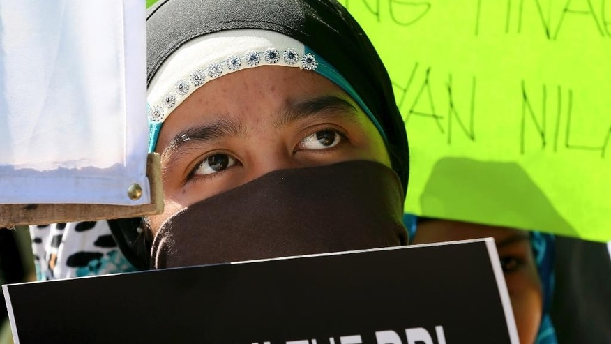 A Filipino Muslim displays a message during a rally at the Lower House to call for the passage of Bangsamoro Basic Law, or BBL in southern Philippines Tuesday, Feb. 10, 2015 at suburban Quezon city, northeast of Manila, Philippines. The BBL deliberation by the Lower House was postponed indefinitely following the botched police operation to capture Malaysian terror suspect Zulkifli bin Hir, known as Marwan which resulted in the killing of 44 elite police commandos. (AP Photo/Bullit Marquez)