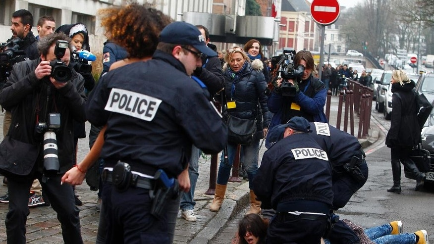 A Femen activist is held down as another is taken away by police officers during their protest Tuesday, Feb. 10, 2015 in front of the Lille courthouse in Lille, northern France, where Dominique Strauss-Kahn goes on trial for sex charges in France. The former head of the International Monetary Fund, whose career went down in flames amid accusations of sexually assaulting a hotel maid in New York, is facing similarly shocking charges in France: aggravated pimping and involvement in a prostitution ring operating out of luxury hotels. (AP Photo/Michel Spingler)