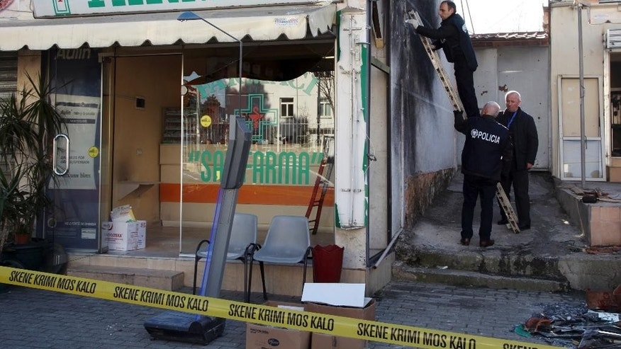 Police officers investigate a drug store belonging to Interior Minister Saimir Tahiri's father damaged by an explosion overnight in Tirana, Albania, Tuesday, Feb. 10, 2015. Another explosion rocked the apartment of a top police officer while anti-mine experts blasted with remote control two TNT explosive ingots found downtown capital. (AP Photo/Hektor Pustina))