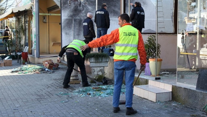 Police officers check the site of an explosion at a drug store, left, belonging to Interior Minister Saimir Tahiri's father and the neighboring house damaged overnight in Tirana, Albania,Tuesday, Feb. 10, 2015. Another explosion rocked the apartment of a top police officer while anti-mine experts blasted with remote control two TNT explosive ingots found downtown capital. (AP Photo/Hektor Pustina))