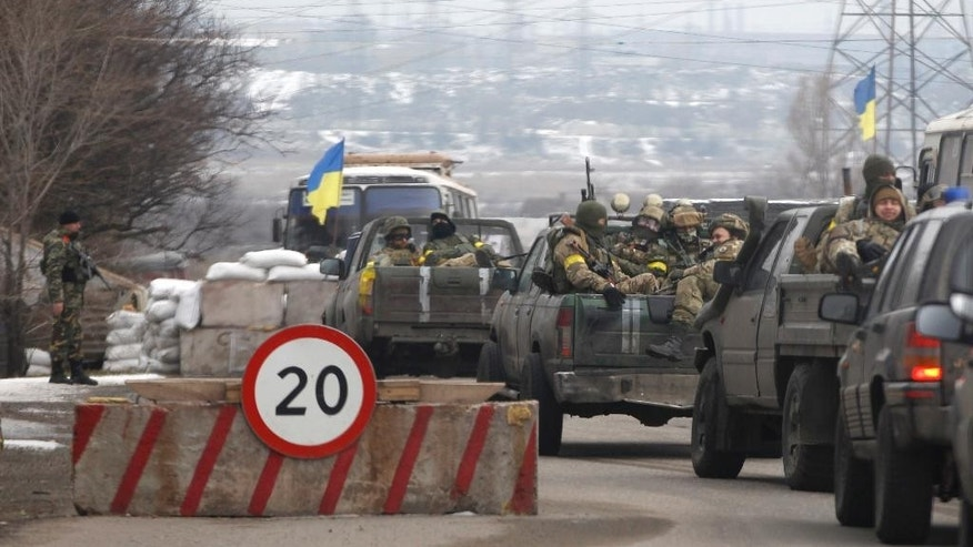 Ukrainian government troops sit in the back of pick-up trucks as they pass a checkpoint near the town of Mariupol, Ukraine, Tuesday, Feb. 10, 2015. The intense fighting, which the U.N. says has killed more than 5,300 people since April, comes ahead of a crucial summit including Western leaders on Wednesday as well as peace talks later Tuesday. The volunteer Azov battalion said on social media on Tuesday that it captured several villages northeast of the strategic port of Mariupol, pushing the rebels closer to the border with Russia. (AP Photo/Petr David Josek)