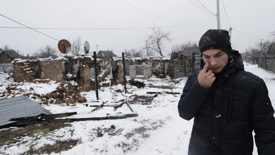 In this picture taken, Monday, Feb. 9, 2015, Ruslan Banin, 18 years old, walks in his neighborhood  in Donetsk, Ukraine. Day and night, mortars and rockets rain down on the rebel stronghold in eastern Ukraine _ mainly in the city's outlying districts, where the poorest people live.  (AP Photo/Petr David Josek)