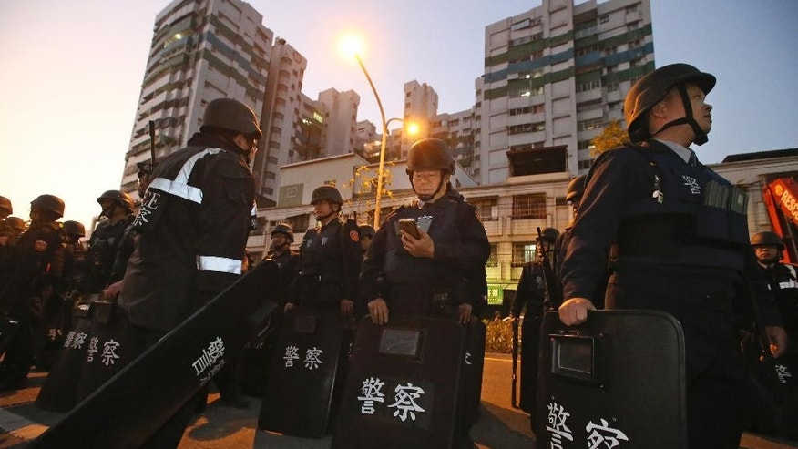 Police in riot gear gather outside of a prison as prisoners hold prison staff hostage inside in Kaohsiung, Taiwan, Wednesday, Feb. 11, 2015. Six inmates took prison staff including the warden hostage, seized guns and ammunition, and demanded safe exit from a prison in southern Taiwan on Wednesday, authorities said. (AP Photo) TAIWAN OUT