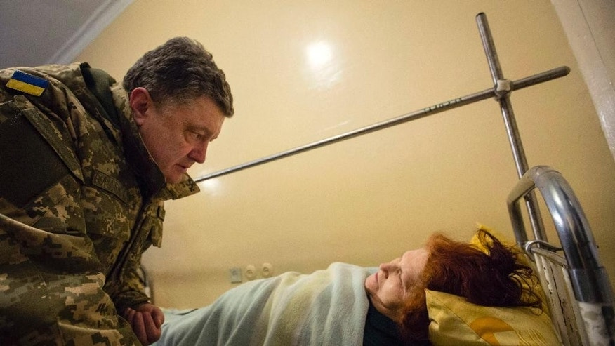 Ukrainian President Petro Poroshenko, left, talks with a wounded victim of an artillery strike in a Kramatorsk hospital, Donetsk region, Ukraine, early Wednesday, Feb. 11, 2015. Fighting intensified Tuesday in eastern Ukraine as pro-Russia rebels and Ukrainian troops sought to extend their gains ahead of crucial peace talks, and the government accused pro-Russia rebels of shelling a town far behind the front lines, killing a dozen people and wounding scores. (AP Photo/Mikhail Palinchak, Pool)