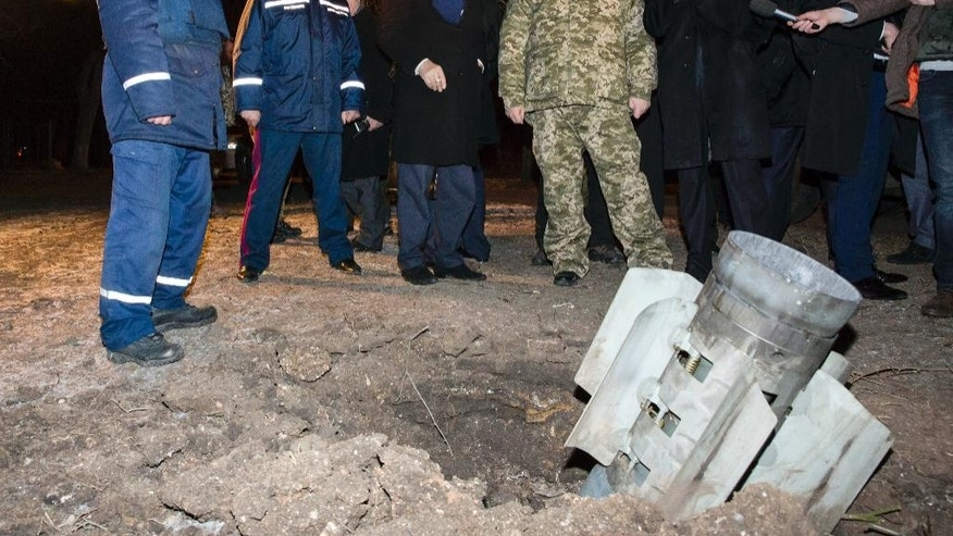 Ukrainian President Petro Poroshenko, fourth left, examines an unexploded rocket in Kramatorsk, Donetsk region, Ukraine, early Wednesday, Feb. 11, 2015. Fighting intensified Tuesday in eastern Ukraine as pro-Russia rebels and Ukrainian troops sought to extend their gains ahead of crucial peace talks, and the government accused pro-Russia rebels of shelling a town far behind the front lines, killing a dozen people and wounding scores.(AP Photo/Mikhail Palinchak, Pool)