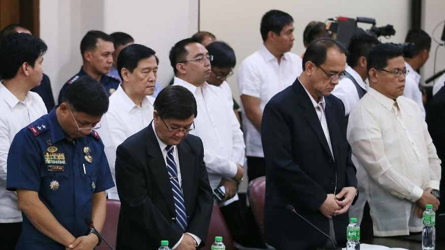 From left, Police Director Getulio Napenas, lawyer Vitaliano Aguirre, lawyer Kristoffer James Purisima and resigned Philippine National Police Chief Gen. Alan Purisima, stand in prayer at the start of the Lower House  probe into the Jan. 25, 2015, incident killing 44 elite police commandos known as SAF (Special Action Force) on Wednesday, Feb. 11, 2015, in Quezon city northeast of Manila, Philippines. Deputy Director General Leonardo Espina said Wednesday that autopsy reports showed some of the commandos were wounded but still alive when shot to death at close range by Muslim insurgents in a recent clash. (AP Photo/Bullit Marquez)