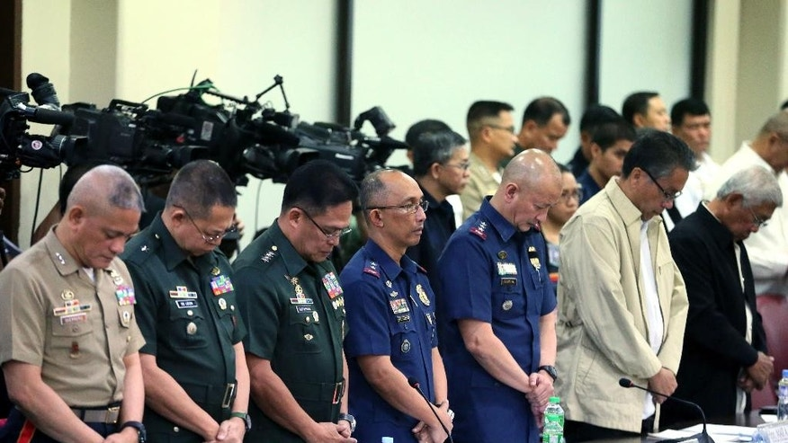 Police, military and government officials stand in prayer at the start of the Lower House probe into the Jan. 25, 2015, incident killing 44 elite police commandos known as SAF (Special Action Force) on Wednesday, Feb. 11, 2015, in Quezon city northeast of Manila, Philippines. Deputy Director General Leonardo Espina said Wednesday that autopsy reports showed some of the commandos were wounded but still alive when shot to death at close range by Muslim insurgents in a recent clash. (AP Photo/Bullit Marquez)