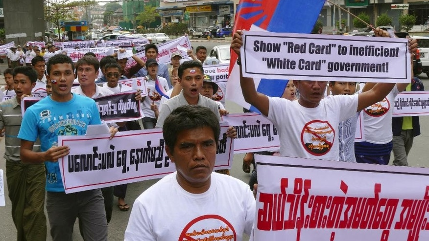 Activists hold placards as they march for a protest Wednesday, Feb.11, 2015 in Yangon, Myanmar. Hundreds of people have demonstrated in Yangon, Myanmar's biggest city, to protest a government decision to allow people without full citizenship, including members of the Rohingya ethnic minority, to vote in an upcoming constitutional referendum. Parliament recently decided to allow temporary identity card holders, known as white card holders, the right to vote in a referendum for constitutional amendments. (AP Photo/Khin Maung Win)