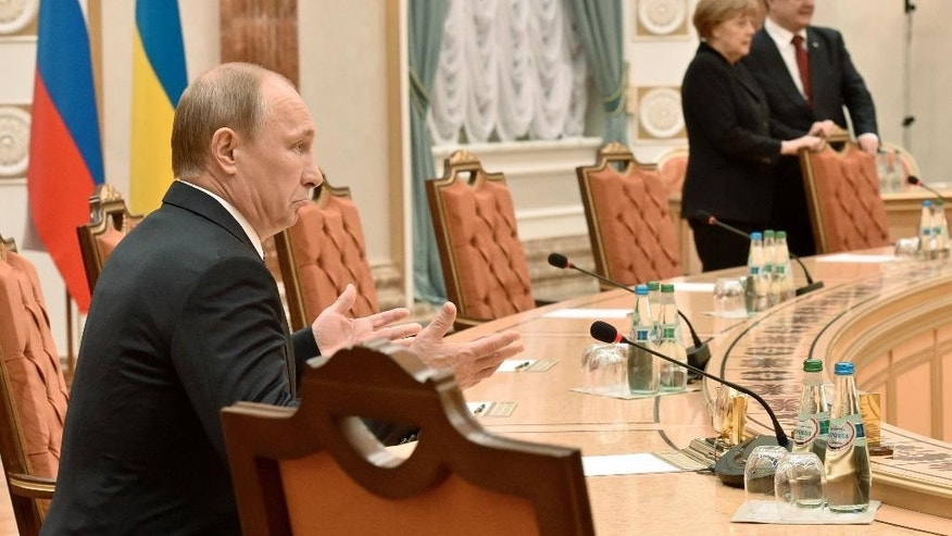 Russian President, Vladimir Putin, left, gestures as German Chancellor, Angela Merkel and Ukrainian President, Petro Poroshenko, stand nearby during a meeting in Minsk, Belarus, Wednesday, Feb. 11, 2015. Leaders of Russia, Ukraine, France and Germany are gathering for crucial talks in the hope of negotiating an end fighting between Russia-backed separatist and government forces in eastern Ukraine. (AP Photo/Kirill Kudryavtsev, Pool)