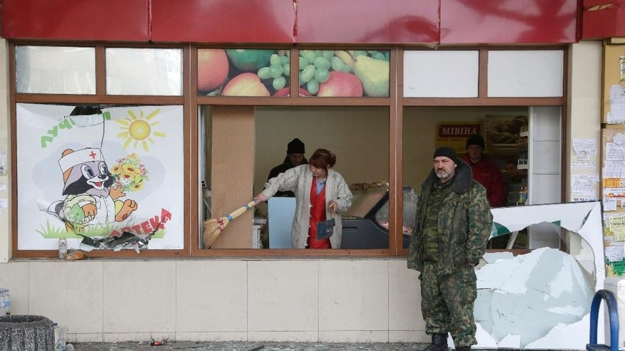 A woman cleans shattered glass after a shop was damaged when a bus station was hit during the recent shelling between Russian-backed separatists and Ukrainian government forces in Donetsk, Ukraine, Wednesday, Feb. 11, 2015. This is at least the third time a bus has been hit in the rebel stronghold but the first time it happens so close to the center, an area of the city which has so far been mostly spared the destruction. (AP Photo/Petr David Josek)