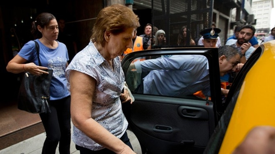 Sara Garfunkel, center, mother of late prosecutor Alberto Nisman, leaves the prosecutor's office that leads the investigation of the mysterious death of her son, after giving her statement to authorities, in Buenos Aires, Argentina,Tuesday, Feb. 10, 2015. Nismans mysterious death came as he was presenting allegations that Argentine President Cristina Fernandez had conspired to protect Iranian officials implicated in the 1994 bombing of a Jewish community center in which 85 people died. Fernandez and Iran have denied the allegations. (AP Photo/Rodrigo Abd)
