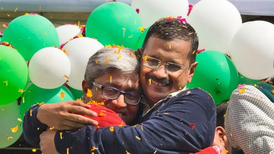 FILE - In this Tuesday, Feb. 10, 2015 file photo, Aam Aadmi Party, or Common Man's Party leaders, Arvind Kejriwal, right, and Ashutosh, hug each other as they celebrate news of their party's performance in New Delhi, India. Kejriwal, the former tax official with the chronic cough and the ill-fitting sweaters, the man who had remade himself into a champion for clean government, seemed lost in the political wilderness. The crusading politician was suddenly a punchline. But on Wednesday, Feb. 11, there was Kejriwal on the front page of nearly every Indian newspaper, celebrating election results that again make him New Delhi's chief minister. Kejriwal and the party he created routed the country's best-funded and best-organized political machine and dealt an embarrassing blow to Prime Minister Narendra Modi. (AP Photo/Manish Swarup, File)