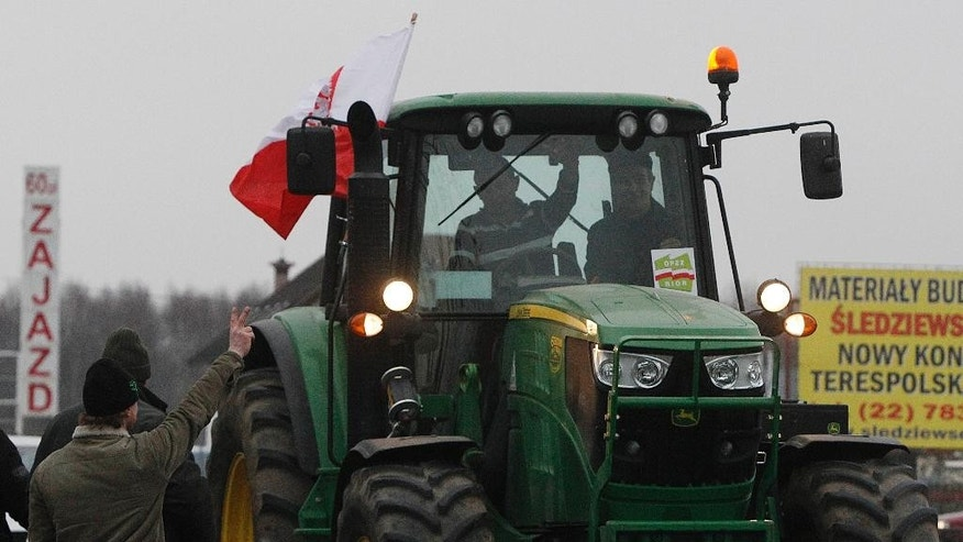 A farmer drives hisr tractor through Koberne on the way to Warsaw, Poland, Wednesday, Feb. 11, 2015. Hundreds of Polish farmers attended the rally, while their leaders were seeking government compensation for crops destroyed by wild boar and profits undercut by Russia's import ban. (AP Photo/Czarek Sokolowski)