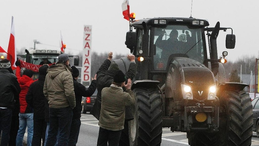 Farmers drive their tractors through Koberne on their way to Warsaw, Poland, Wednesday, Feb. 11, 2015. Hundreds of Polish farmers attended the rally, while their leaders were seeking government compensation for crops destroyed by wild boar and profits undercut by Russia's import ban. (AP Photo/Czarek Sokolowski)