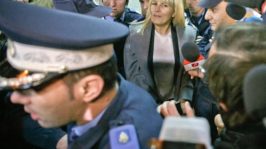 In a photo taken on Tuesday, Feb. 10, 2015, Elena Udrea a 41-year-old Romanian politician who gained notoriety due to her close relationship with Traian Basescu, Romania's president from 2004 to 2014 is escorted by policemen as she exits, handcuffed, the anti-corruption prosecutor's office in Bucharest, Romania. Udrea, a former Romanian tourism minister and presidential candidate was detained for 24 hours late Tuesday after she entered the anti-corruption prosecutor's office to answer charges of money laundering and influence peddling.(AP Photo/Vadim Ghirda)