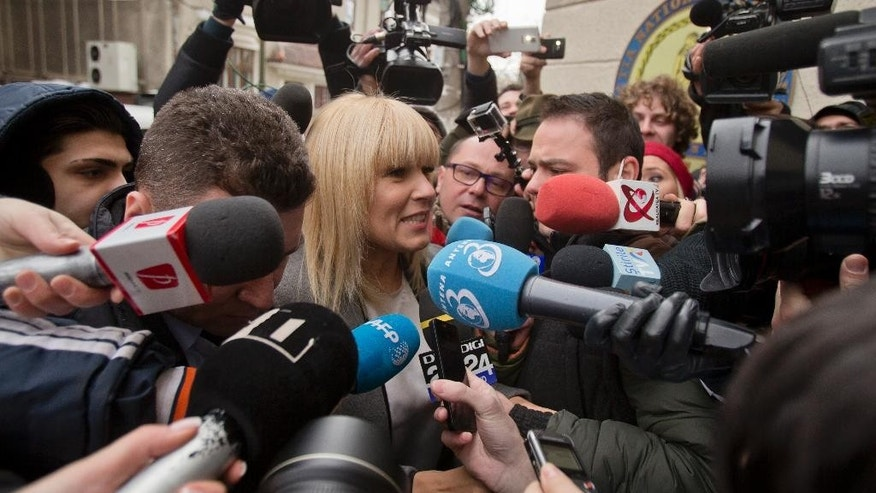 In a photo taken on Tuesday, Feb. 10, 2015, media surrounds Elena Udrea a 41-year-old Romanian politician who gained notoriety due to her close relationship with Traian Basescu, Romania's president from 2004 to 2014, as she arrives at the anti-corruption prosecutor's office in Bucharest, Romania. Udrea, a former Romanian tourism minister and presidential candidate was detained for 24 hours late Tuesday after she entered the anti-corruption prosecutor's office to answer charges of money laundering and influence peddling.(AP Photo/Vadim Ghirda)