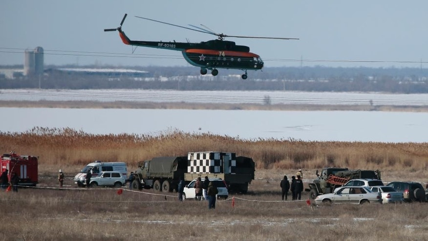 Rescue workers inspect the area where a Russian military jet crashed while on a training mission in the Volgograd region in southern Russia, Wednesday, Feb. 11, 2015. The Su-24 bomber crashed while approaching its base and the fate of its two crew members have remained unknown. (AP Photo/Dmitry Rogulin)