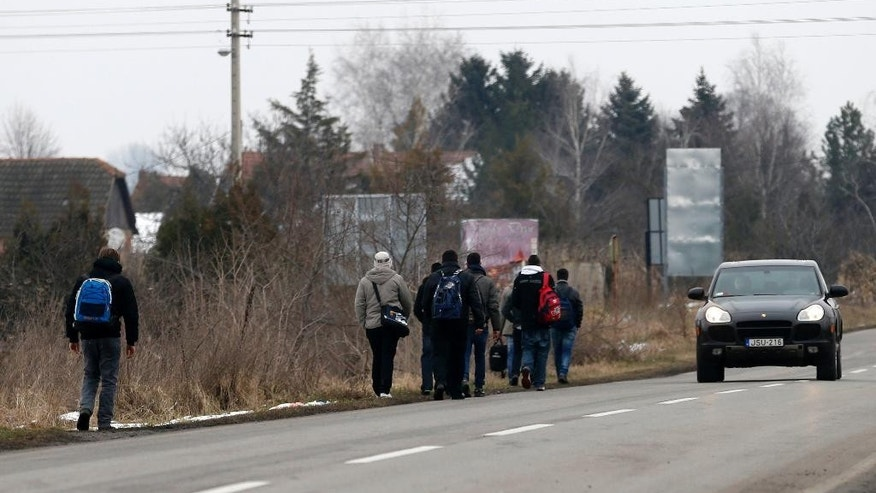 Kosovo migrants walk by the road near the northern Serbian town of Subotica, not far from the border between Serbia and Hungary, Tuesday, Feb. 10, 2015. Serbian security forces have stepped up patrols and deployed an elite unit on the border with Hungary, trying to prevent an illegal flow of migrants that has triggered alarm in many European Union countries. (AP Photo/Darko Vojinovic)
