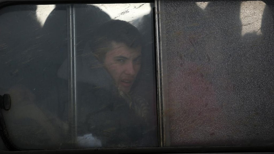 A Kosovo migrant looks through the window of a police van after being detained by Serbian border police near the northern Serbian town of Subotica, not far from the border between Serbia and Hungary, Tuesday, Feb. 10, 2015. Serbian security forces have stepped up patrols and deployed an elite unit on the border with Hungary, trying to prevent an illegal flow of migrants that has triggered alarm in many European Union countries. (AP Photo/Darko Vojinovic)