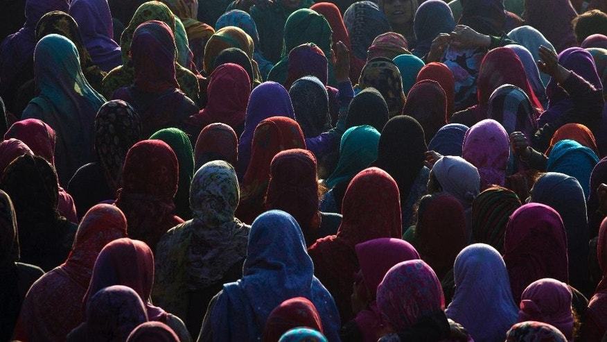 Kashmiri women participate in the funeral procession of Farooq Ahmed Bhat in Palhalan, some 35 kilometers (22 miles) north of Srinagar, Indian controlled Kashmir, Tuesday, Feb. 10, 2015. Hundreds of angry protesters clashed with Indian authorities on Tuesday at the funeral of the young man killed during a demonstration in disputed Kashmir. Separatists called for a daylong strike in the tense Himalayan territory. (AP Photo/ Dar Yasin)