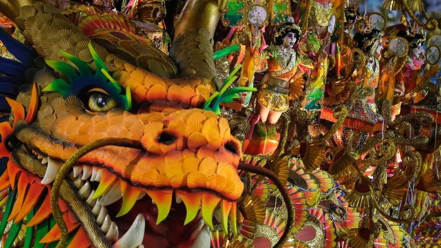 FILE - In this March 3, 2014, file photo, performers from the Beija-Flor samba school parade on a float during carnival celebrations at the Sambadrome in Rio de Janeiro, Brazil. Rio's O Globo newspaper, one of Brazil's biggest, reported on Feb. 2015, that the samba group received substantial funding from Equatorial Guinea's President Teodoro Obiang Nguema, one of Africa's most notorious dictators, an allegation that has sparked controversy on the eve of Brazil's Carnival celebrations (AP Photo/Felipe Dana, File)