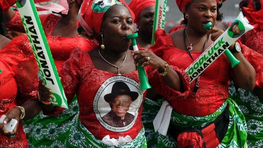 FILE- In this Thursday, Jan. 8, 2015 file photo, supporters of Nigerian President Goodluck Jonathan dance, during an election campaign rally, at Tafawa Balewa Square in Lagos, Nigeria. The six-week delay in Nigeria's presidential election has raised red flags both in the international community and among local opposition political groups, with many concerned about the independence of the country's electoral commission and whether the military hierarchy had too much say in the matter. President Goodluck Jonathan and his chief rival, former military dictator Muhammadu Buhari, are facing off in what is probably the tightest presidential contest in the history of Nigeria, Africa's most populous nation and its economic powerhouse, so any change like moving back election day is seen as drastic and a possible game-changer.  (AP Photo/Sunday Alamba file)