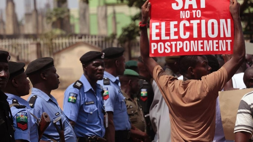 FILE- In this Saturday, Feb. 7, 2015 file photo, a protestor holds a banner as Nigerian security forces look on, during a protest in Abuja, Nigeria. The six-week delay in Nigeria's presidential election has raised red flags both in the international community and among local opposition political groups, with many concerned about the independence of the country's electoral commission and whether the military hierarchy had too much say in the matter. President Goodluck Jonathan and his chief rival, former military dictator Muhammadu Buhari, are facing off in what is probably the tightest presidential contest in the history of Nigeria, Africa's most populous nation and its economic powerhouse, so any change like moving back election day is seen as drastic and a possible game-changer.  (AP Photo/Lekan Oyekanmi file)
