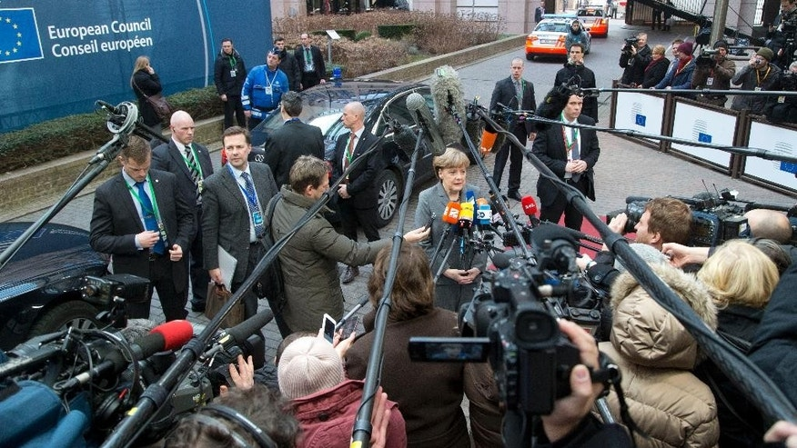 German Chancellor Angela Merkel, center, speaks with the media as she arrives for an EU summit in Brussels on Thursday, Feb. 12, 2015. European Union leaders on Thursday said the full respect of the planned weekend cease-fire in eastern Ukraine will be essential before there could be a change in the sanctions regime imposed on Moscow. (AP Photo/Michel Euler)