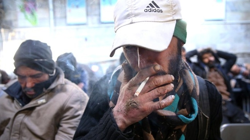Feb. 3, 2015: A drug addict smokes cigarette at drop-in center and shelter south of Tehran, Iran.